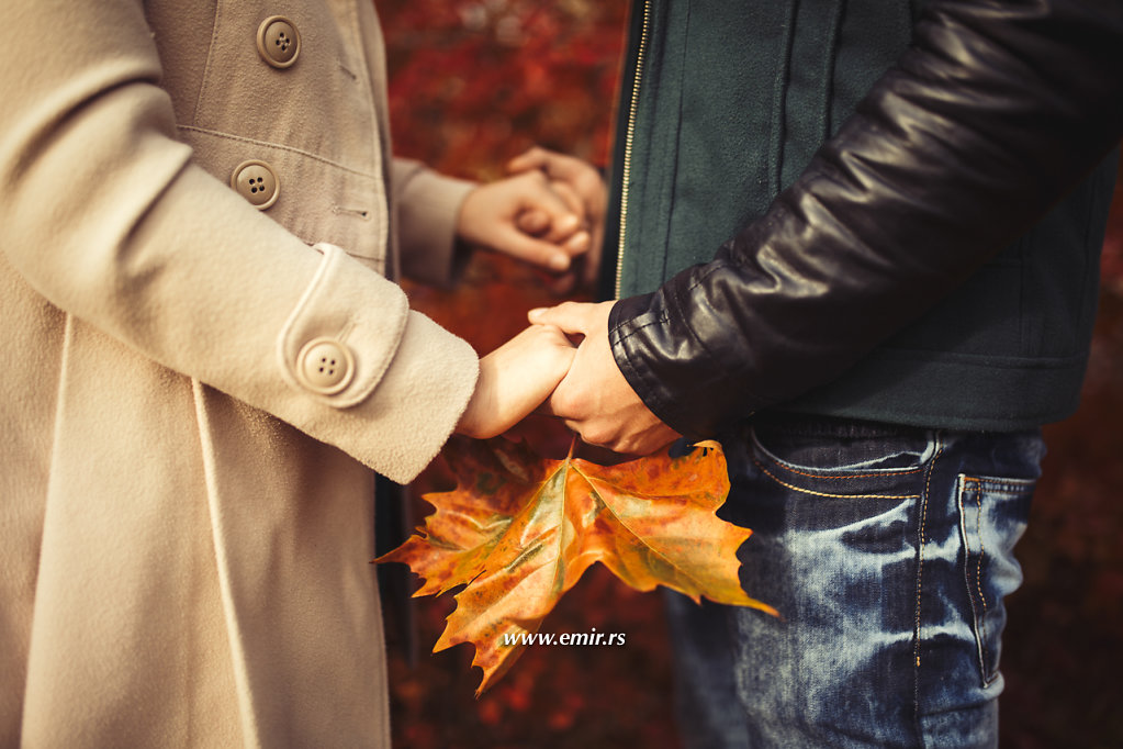Couple holding hands and autumn leaf  in the park.