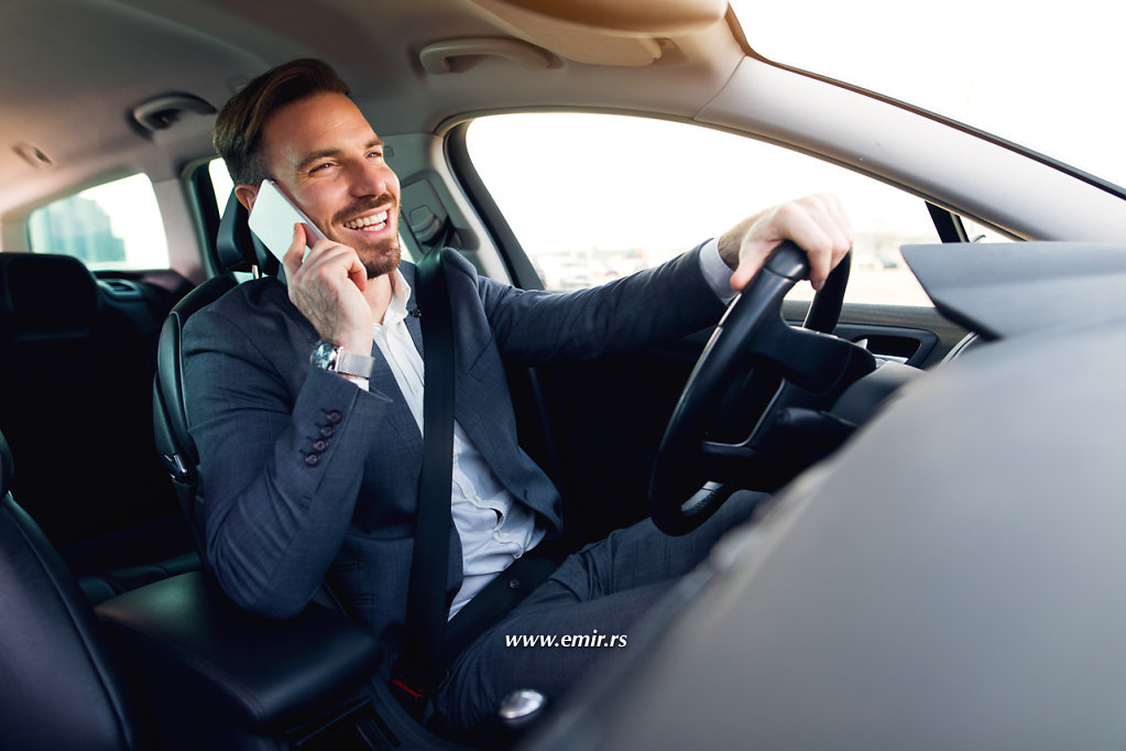 Businessman using mobile phone while driving a car